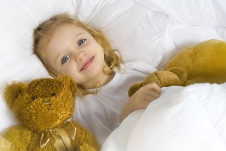 Little blond girl wearing white blouse in white bedchlothes Stock Photo - 3084385