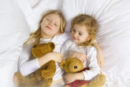 pijama: Little chica rubia llevaba blusa blanca en blanco bedchlothes