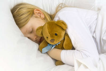toy bear: Little blond girl wearing white blouse in white bedchlothes Stock Photo