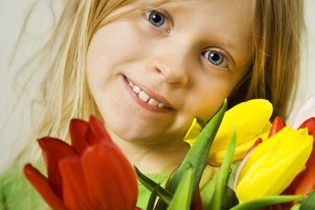 Little blond girl and bunch of colorful tulips photo