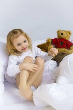 Little blond girl wearing white blouse in white bedchlothes Stock Photo - 3114695
