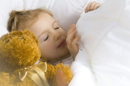 Little blond girl wearing white blouse in white bedchlothes Stock Photo - 3114696