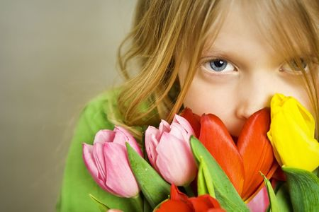 Little blond girl and bunch of colorful tulips