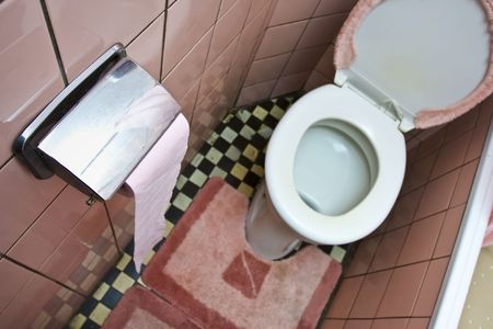 defecate: Dirty old  toilet with pink ceramic tiles