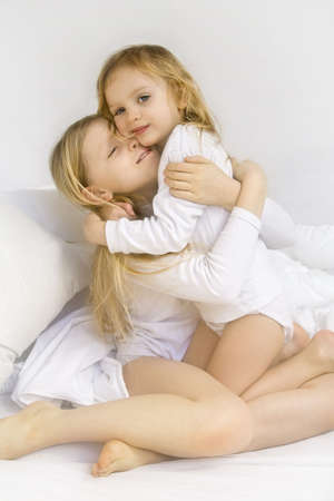 Little blond girl wearing white blouse in white bedchlothes photo