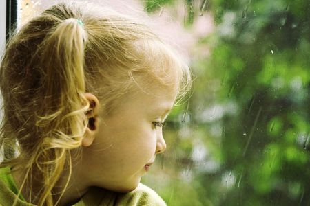 Little girl sitting near the window in the rainy day photo
