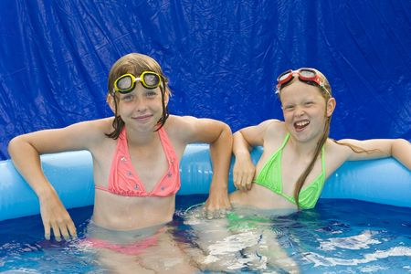 kids swimming pool: Little girls playing in th blue paddling pool