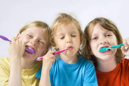 Little girl wearing colorful t-shirts brushing teeth