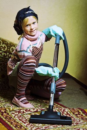 Little girl cleaning an old dirty house photo