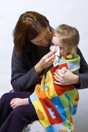 tosiendo: Sick Girl litle en las rodillas de su madre