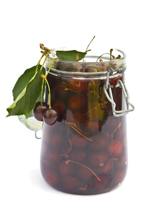 Dark berries of cherry in glass jar  photo