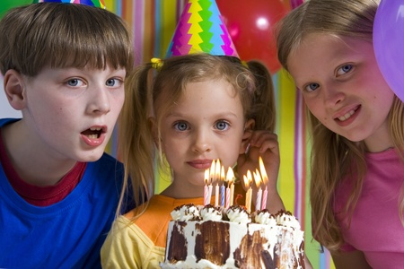 Happy children with birthday cake on a striped background photo