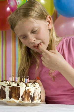 girl blowing: Happy children with birthday cake on a striped background
