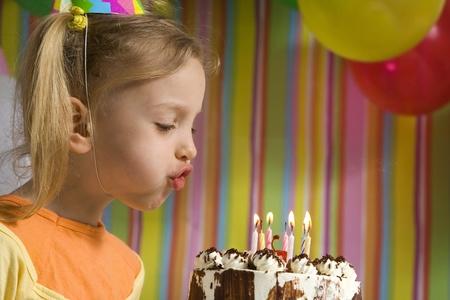 velas de cumpleaños: Niños felices con pastel de cumpleaños en un fondo rayado Foto de archivo