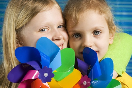 pinwheel: Children with rainbow pinwheel on a striped blue background