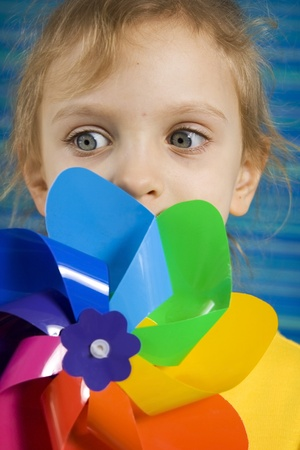 Children with rainbow pinwheel on a striped blue background photo