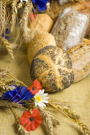 Bread and rolls with corn and field flowers photo