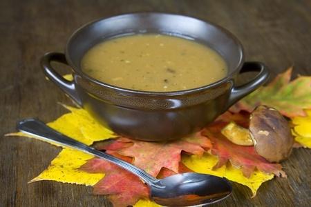 mushroom soup: Mushroom soup and autumnal leaves on a brown table