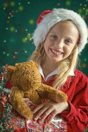 Little girl dressed up as Santa on green background photo