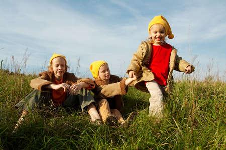 gnomos: Ni�os que usan los casquillos amarillos que juegan en prado oto�al