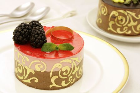 Chocolate and strawberry layer mousse cake, decorated with mulberries