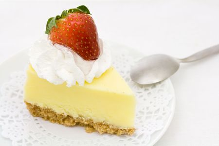 Cheesecake decorated with whipped cream and strawberry