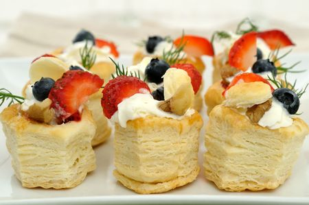 Fruit vol au vent stuffed with whipped cream and topped with strawberry slices and blueberry