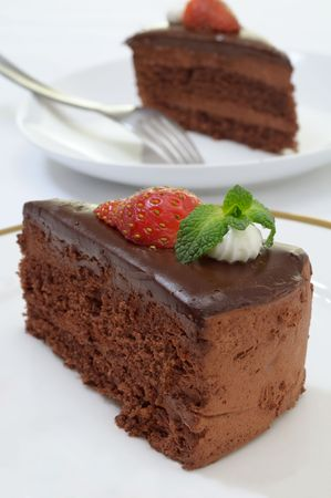 Chocolate cake slice decorated with a strawberry and mint leaves Stock Photo