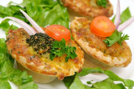 Small vegetable quiche decorated with onion, broccoli, tomato slice and parsley