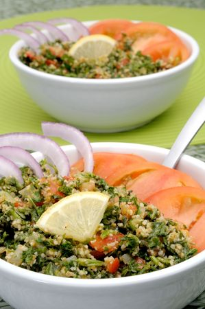 Tabbouleh with tomato and onion slices and lemon in white bowls Stock Photo