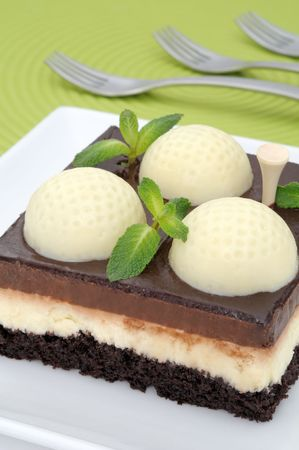 fanciful: Fanciful chocolate golf cake with mint leaves on a green mat with forks