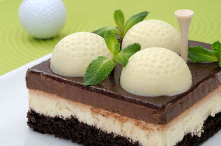 Fanciful chocolate golf cake with mint leaves on a green mat Stock Photo