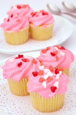 Small pink cupcakes decorated with heart candies