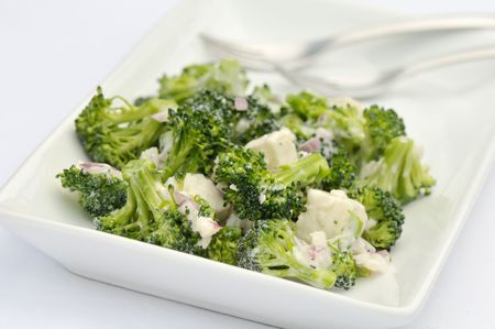 Broccoli and feta salad with shallots and caesar dressing on white platter