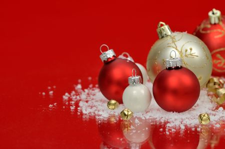 Red and white baubles with snow and jingle bells on red background Stock Photo
