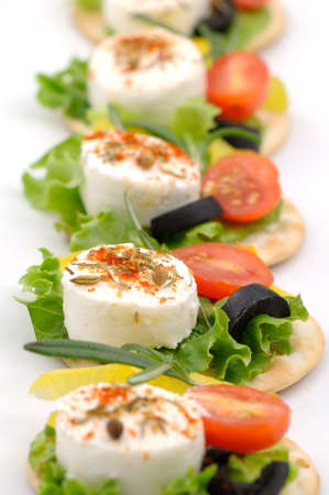food buffet: Small goat cheese slices on cracker with salad leaf, tomato, olive and spices