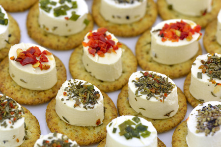white party: Close-up of cheese appetizers decorated with spices and vegetable Stock Photo