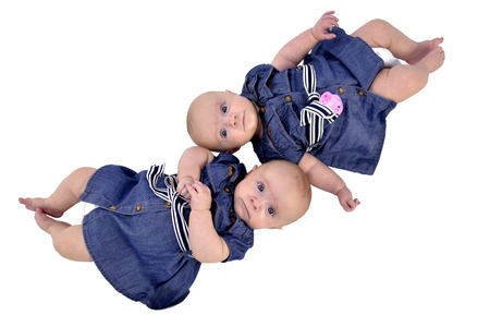 Six month twin sisters on white background, lying top-to-tail photo