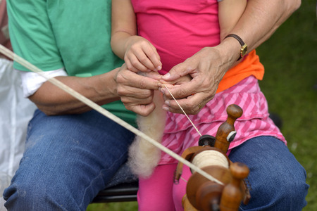 Old lady teaches her little daughter doing handicrafts Stock Photo