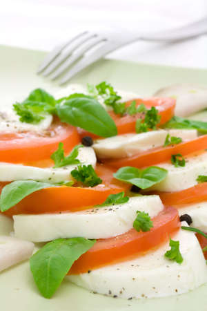 Caprese salad on a green plate, decorated with herbs. Shallow depth of field Stock Photo