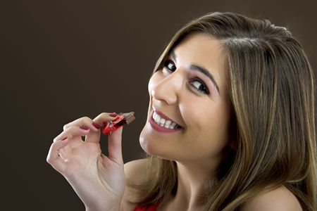 A beautiful happy woman satisfying a chocolate candy photo