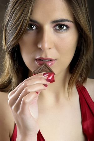 A beautiful woman satisfying a chocolate candy