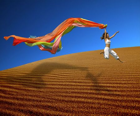 Beautiful woman jumoping over the sand dunes with a colored scarf Stock Photo - 1092526