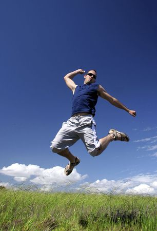 Man make a big jump on a green meadow Stock Photo - 1092530