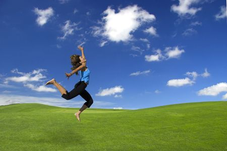Beautiful athletic woman jumping on a green field photo