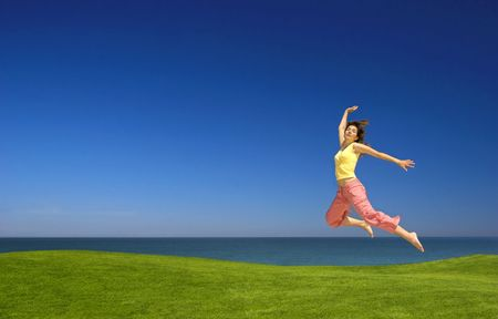 Beautiful woman jumping on a green field photo