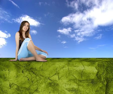 Beautiful athletic woman with different poses seated on a green wall photo