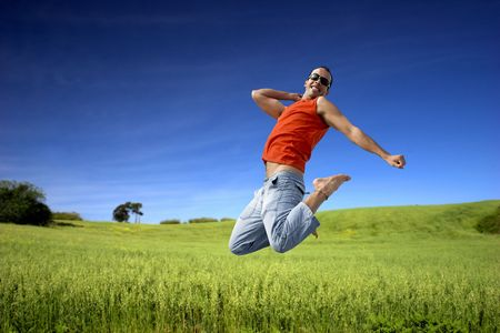 Man jumping on a green meadow with a beautiful cloudy sky Stock Photo - 1320502