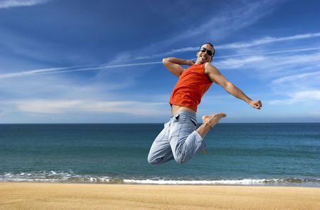 Man jumping on a the beach with a beautiful cloudy sky Stock Photo - 1320490
