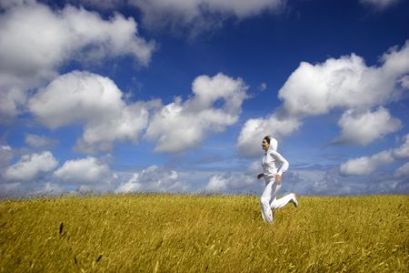 Beautiful woman running on a golden meadow Stock Photo - 1320492